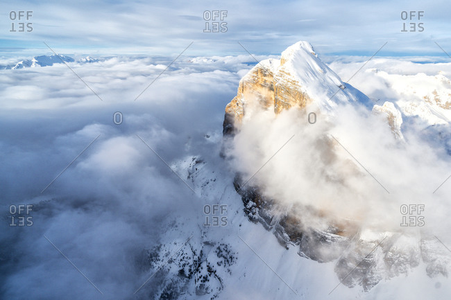 Snow covered Tofana di Rozes above the clouds, aerial view, Dolomites, Belluno province, Veneto, Italy, Europe