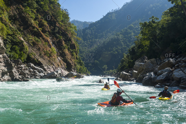 Kayakers negotiate their way through whitewater rapids on the Karnali River in west Nepal, Asia