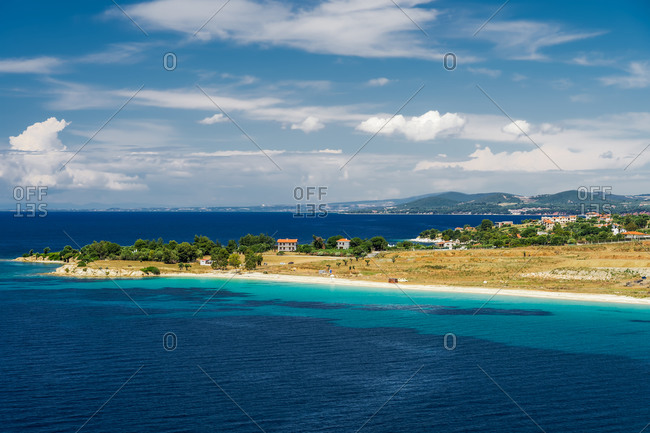 Mediterranean landscape with low-rise houses by an empty sandy beach with calm waters at Sithonia Peninsula, Chalkidiki, Greece, Europe