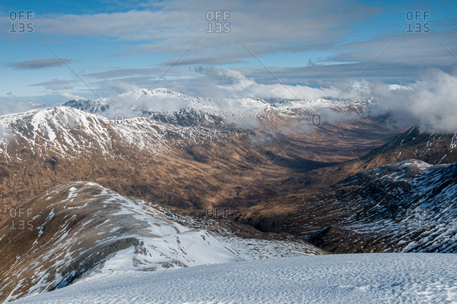 Looking down into Fionngleann in winter from Brothers Ridge in Kintail with the hills of Wester Ross in distance, Highlands, Scotland, United Kingdom, Europe