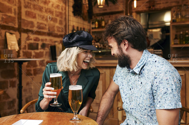 Couple in their 30s having a drink at a bar