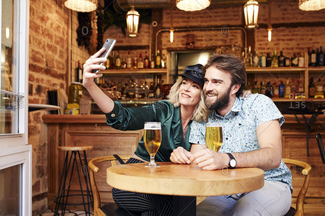 Couple in their 30s taking a selfie together at a bar