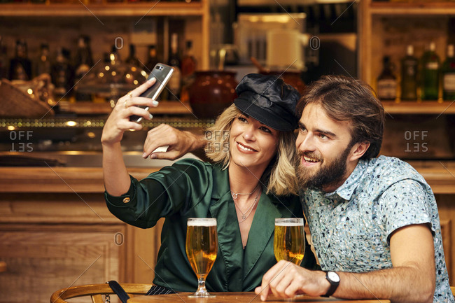 Couple in their 30s taking a selfie together with their drinks