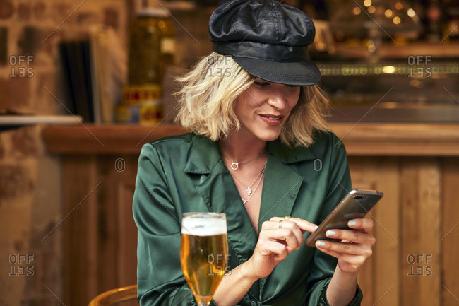 Blonde woman in her 30s looking at her mobile phone and smiling