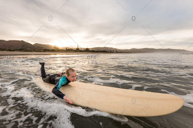 Young girl paddling on a surfboard at sundown on the coast of New Zealand