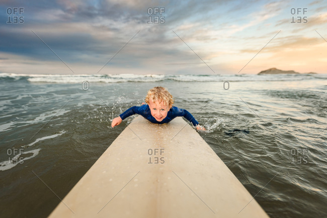 Boy with blonde curly hair paddling on a surfboard at sundown on the coast of New Zealand