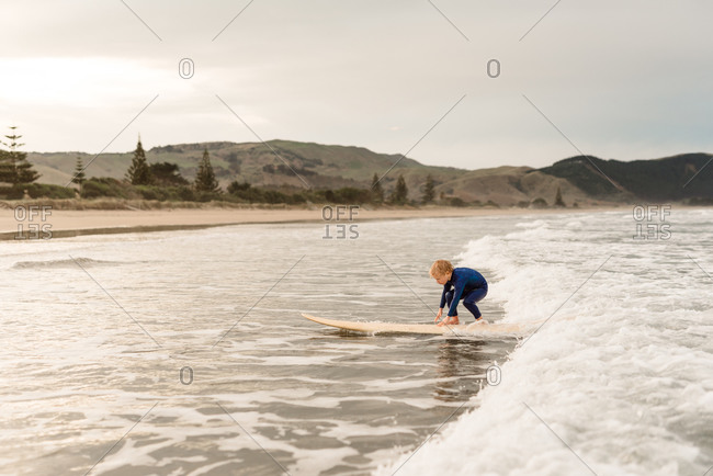 Young boy standing up on surfboard