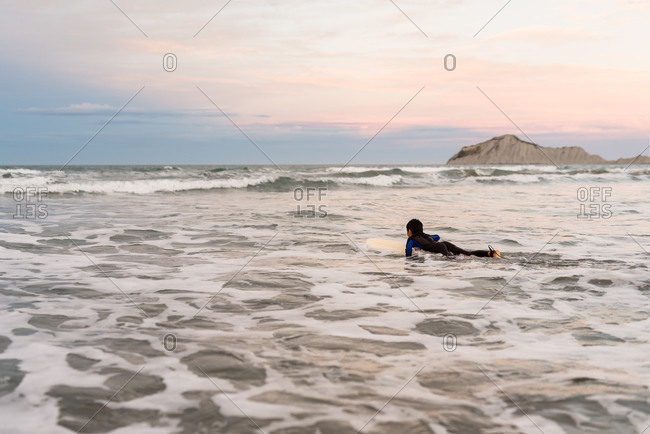 Boy in the ocean paddling on a surfboard at sundown on the coast of New Zealand