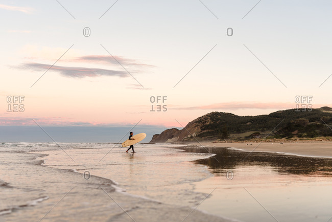 Boy carrying a surfboard at sundown on the coast of New Zealand