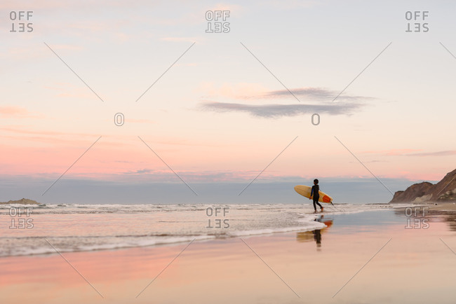 Boy carrying a surfboard into the ocean at sundown on the coast of New Zealand
