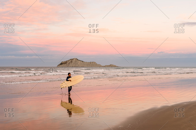 Boy on a beach with surfboard at sundown on the coast of New Zealand