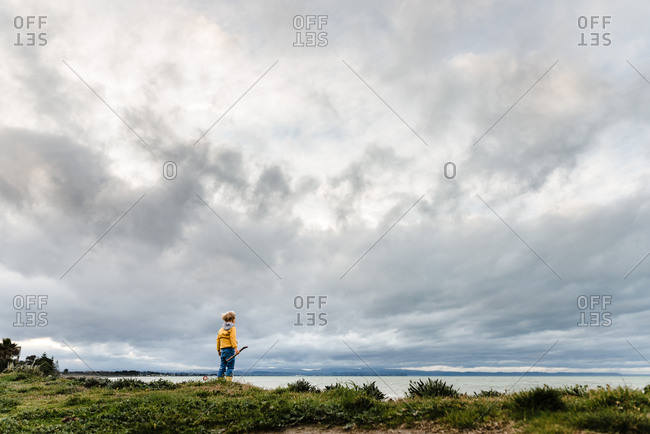 Blonde boy holding stick and overlooking the ocean on cloudy day