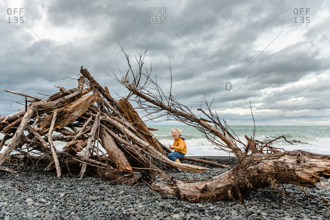 Blonde playing on rocky beach with driftwood by the ocean on cloudy day