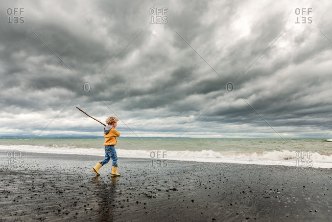 Boy with large stick playing on beach under cloudy sky