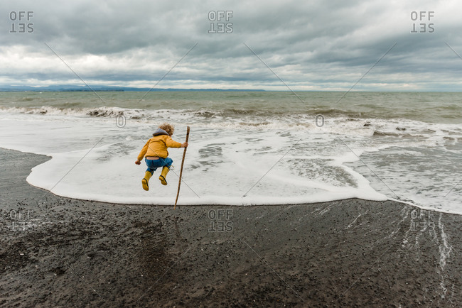 Boy with large stick jumping over waves on beach under cloudy sky