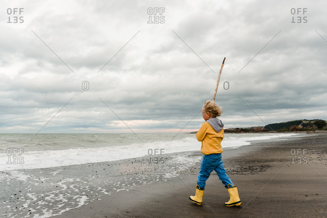 Boy playing with large stick on beach under cloudy sky on the coast of New Zealand