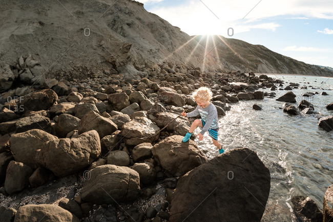 Curly haired boy climbing on rocks on the coast of New Zealand