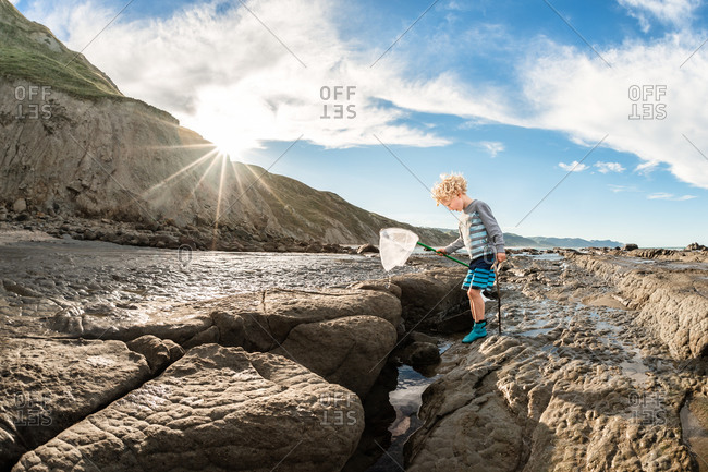 Curly haired boy with net climbing on rocks on the coast of New Zealand