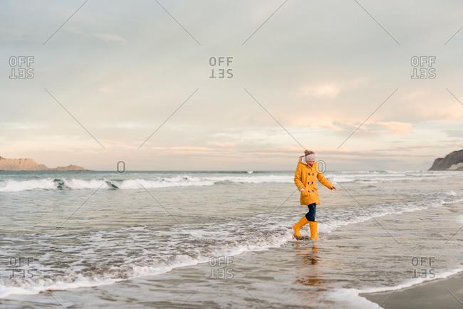 Tween girl wearing yellow jacket and boots walking in the ocean tide