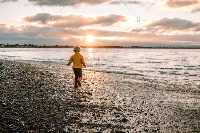 Little boy running on a rocky beach at sunset