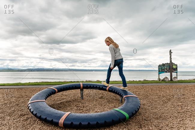 Tween girl climbing on round playground equipment