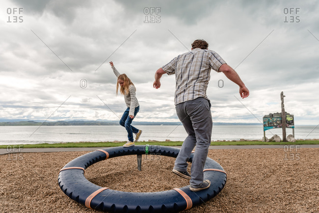 Tween girl and her dad balancing on round playground equipment
