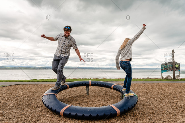 Father and tween daughter balancing on round playground equipment