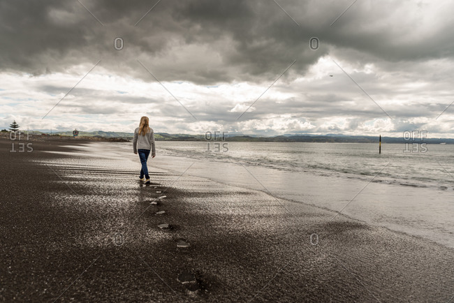 Rear view of a tween girl walking on beach under stormy sky