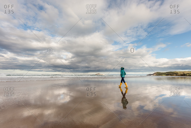 Girl walking on beach with clouds reflecting in the water