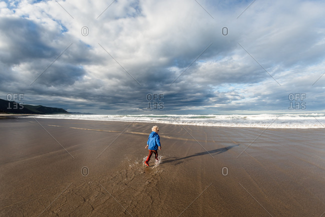 Rear view of boy wearing boots and jacket while running through water on a beach