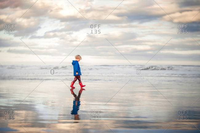 Curly haired boy walking alone on beach wearing jacket and boots