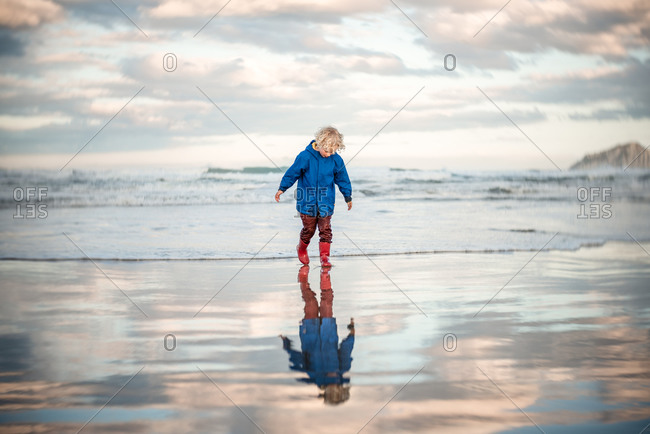 Curly haired boy looking down while stomping in water on beach with his boots