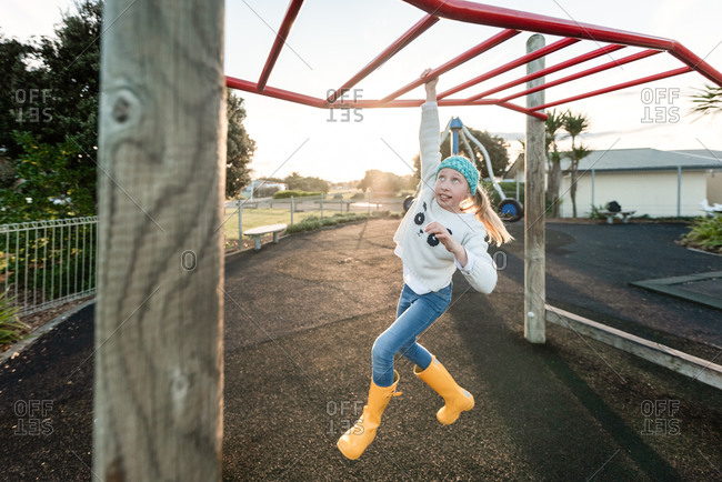 Tween girl climbing on monkey bars on a playground