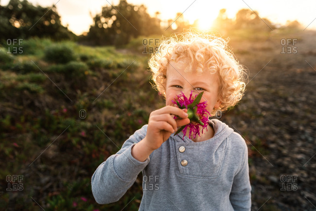 Boy with curly blonde hair smelling a pink flour at sunset