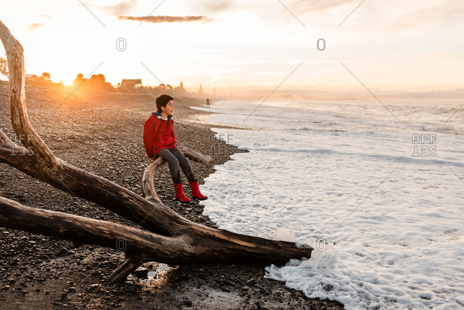 Tween boy sitting on driftwood overlooking the ocean