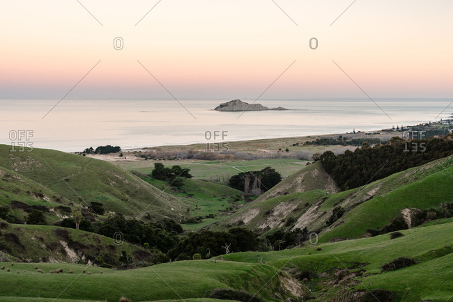 View of Te Motu-o-Kura island and green hills in New Zealand at sundown