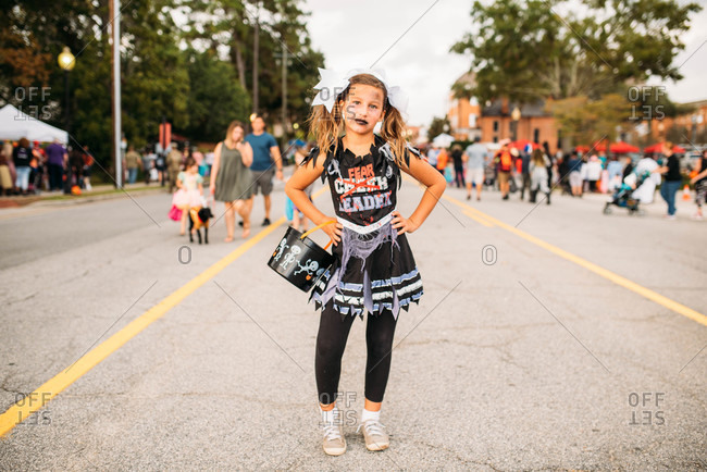 Girl dressed as a zombie cheerleader for a Halloween parade