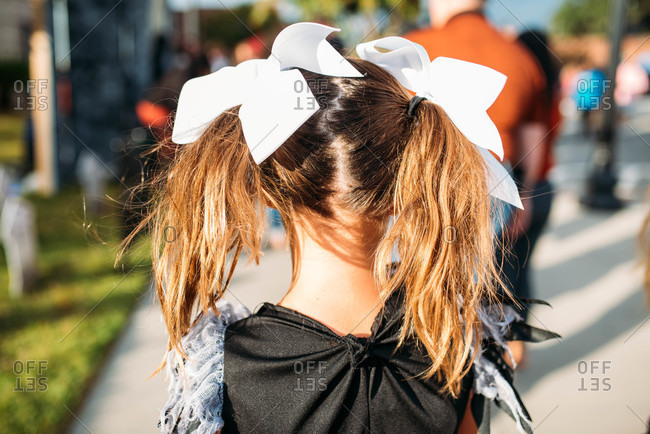 Rear view of little girl wearing costume with large white bows on her pigtails