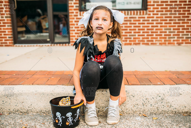 Girl dressed as a zombie cheerleader for Halloween sitting on curb with her candy bucket