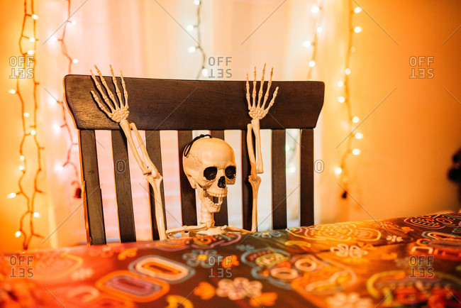 Skeleton decoration sitting at a dining room chair at Halloween