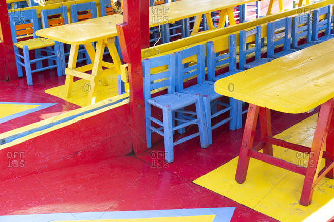 Colorful table and chairs on tour boats in the Xochimilco area, Mexico City, Mexico