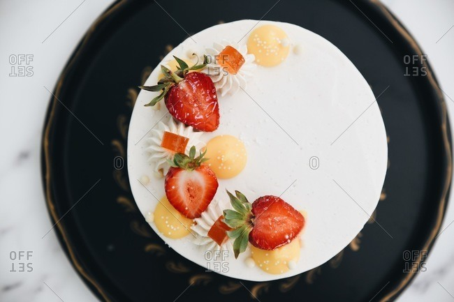 Overhead view of a white cake topped with strawberries