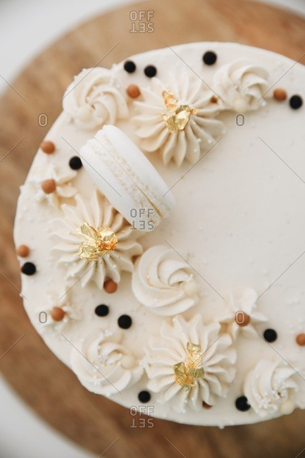 Overhead view of a white cake topped with a macaron and gold leaf