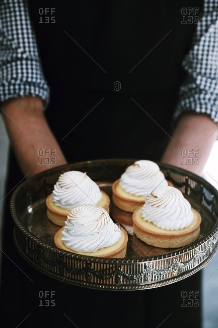 Person holding four individual sized desserts on an antique tray