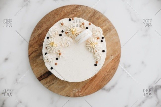 White cake topped with a macaron and gold leaf on a wooden board