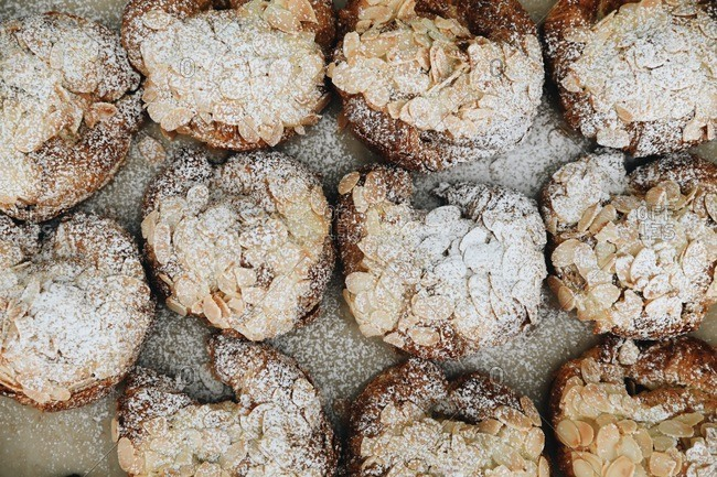 Overhead view of almond pastries covered in powdered sugar