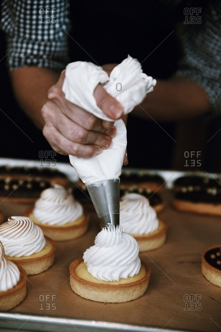Baker topping individual sized custard tarts with meringue