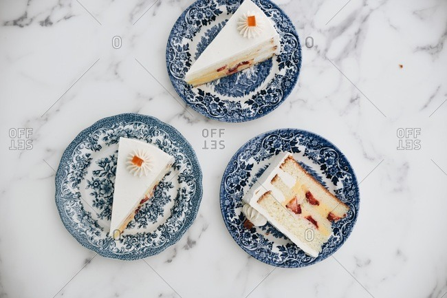 Slices of white cake layered with custard and strawberries on fancy blue plates