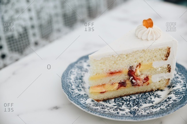 Slice of white cake layered with custard and strawberries on a fancy blue plate