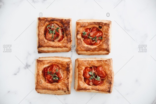 Tomato puff pastry tarts on white marble surface